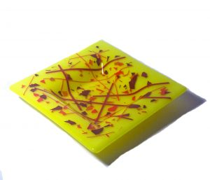 Square yellow dish accented with red and orange